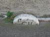 Ancienne borne au trois-quart enterrée dans le trottoir, au pied d'une vieille maison. A gauche, le