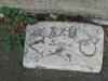 Ancienne borne au trois-quart enterrée dans le trottoir, au pied d'une vieille maison. Elle marquait la limite entre les communes de Vand?uvre et de Genève.